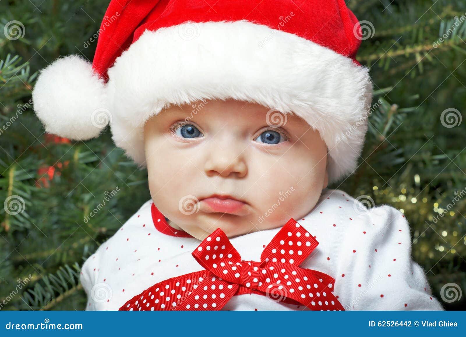 佩带圣诞老人帽子和圣诞树的女婴