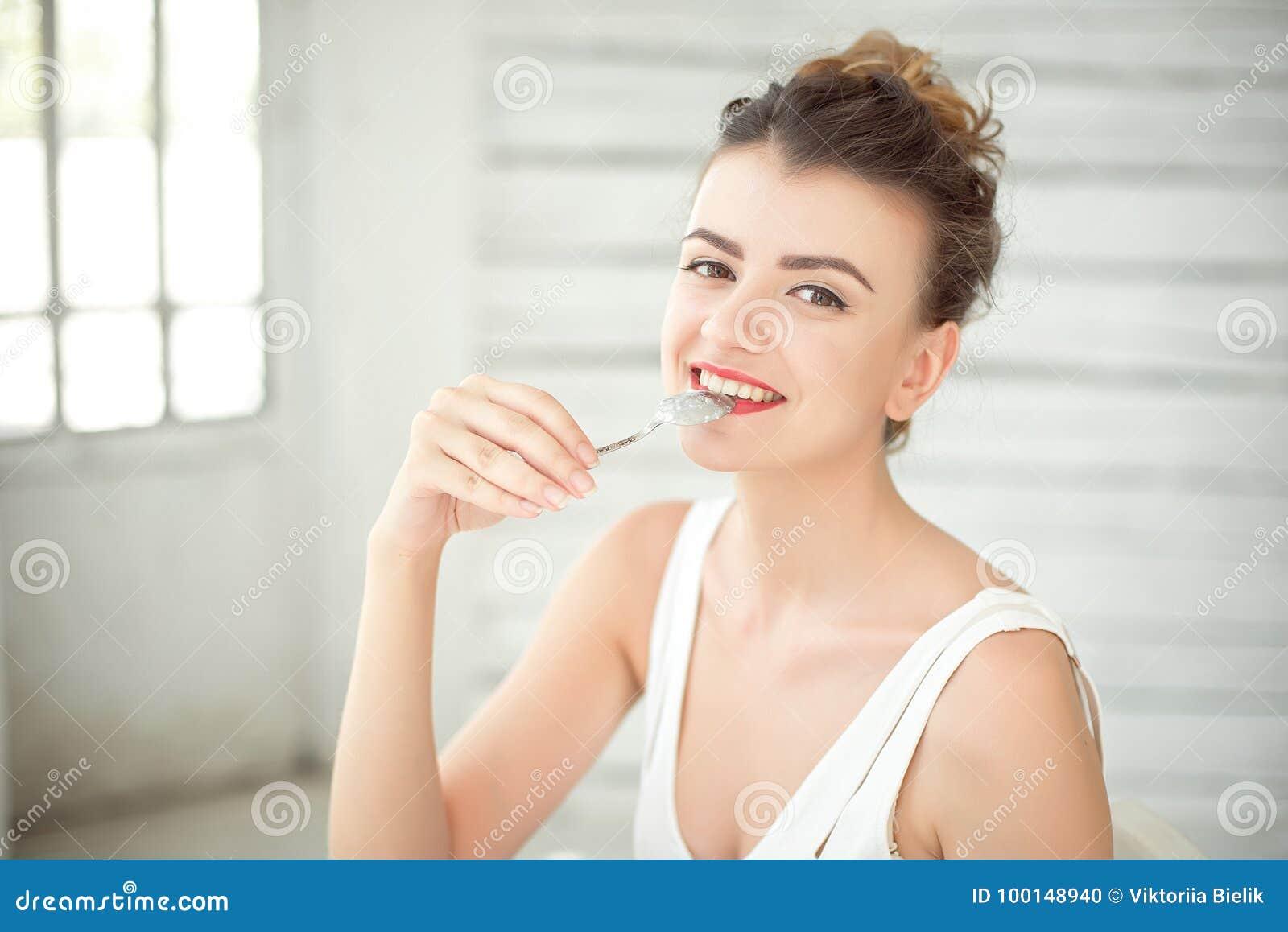 佩带在有匙子的白色汗衫的愉快的美丽的深色头发的妇女半身画象在嘴