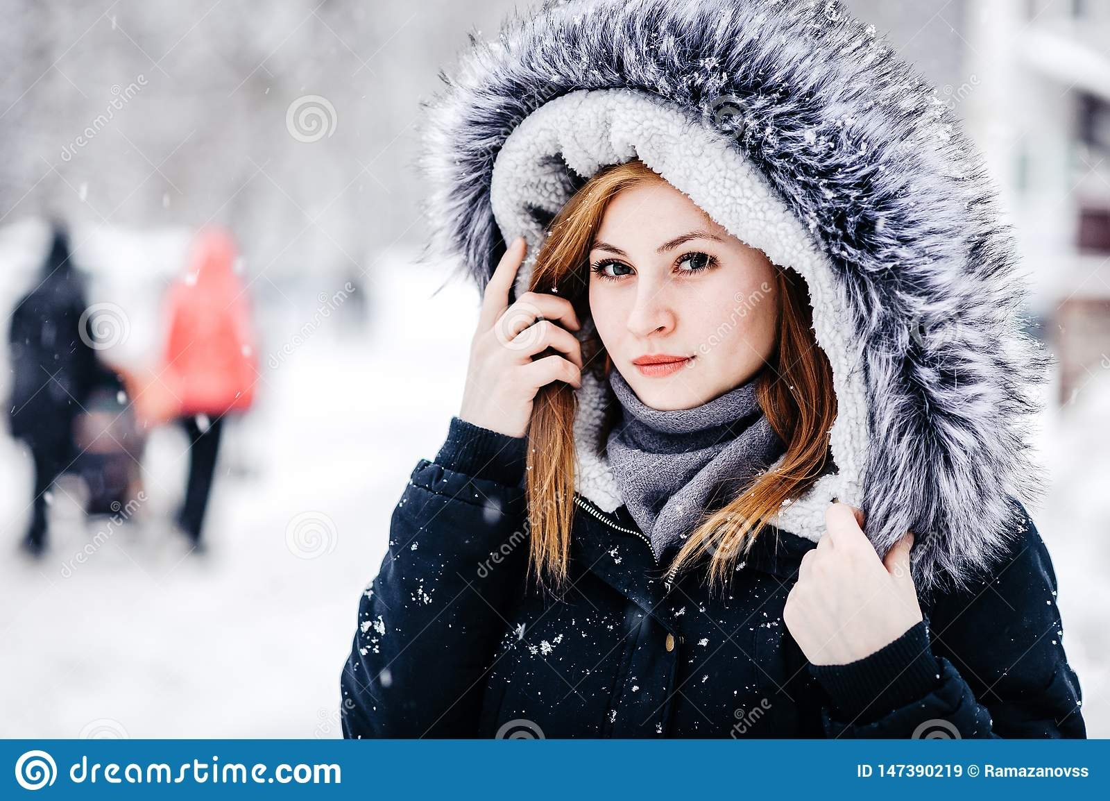 佩带在有敞篷的黑夹克的年轻美女室外画象 式样摆在街道 寒假概念