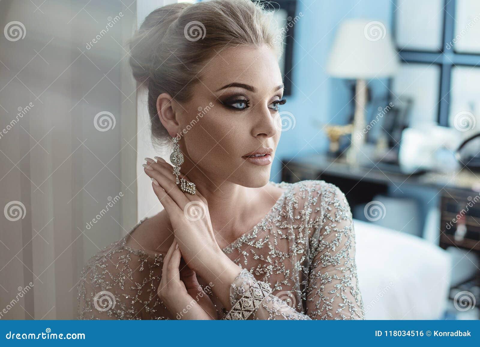 佩带昂贵的首饰的一名端庄的妇女的特写镜头画象