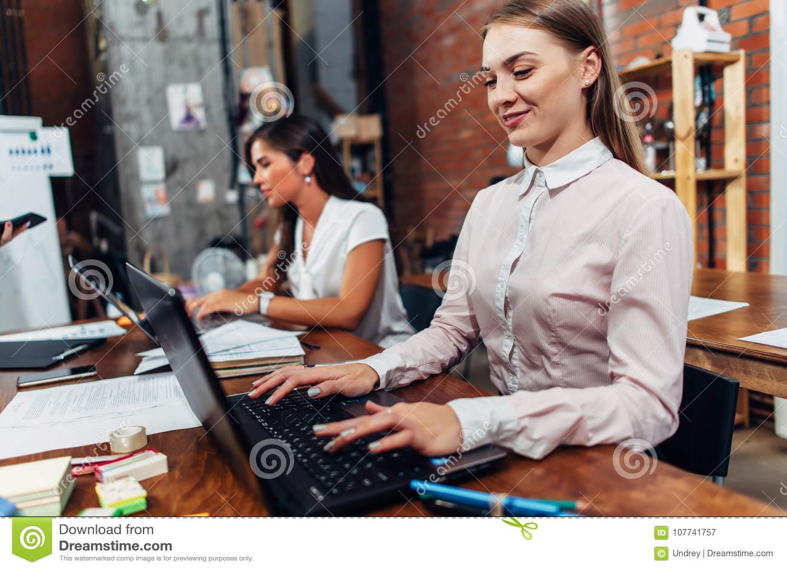 佩带正式工作服的友好的女性办公室工作者键入在运转在创造性的机构中的膝上型计算机键盘