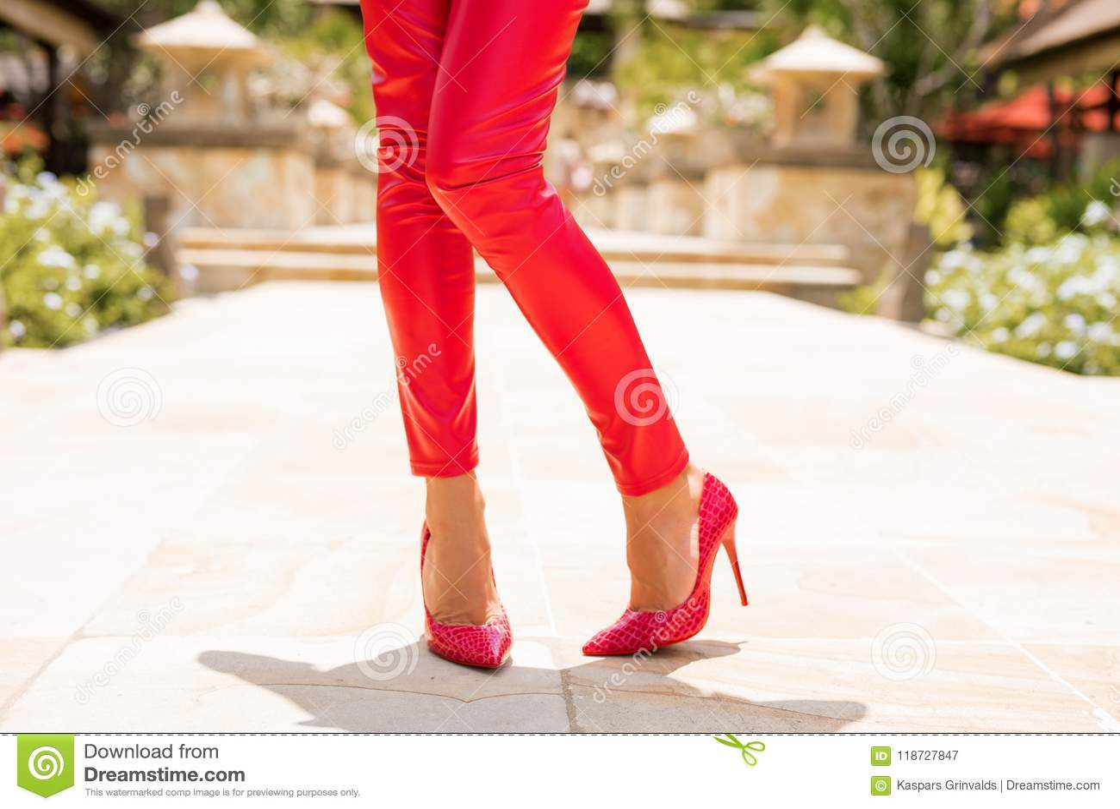 佩带红色裤子和高跟鞋的妇女