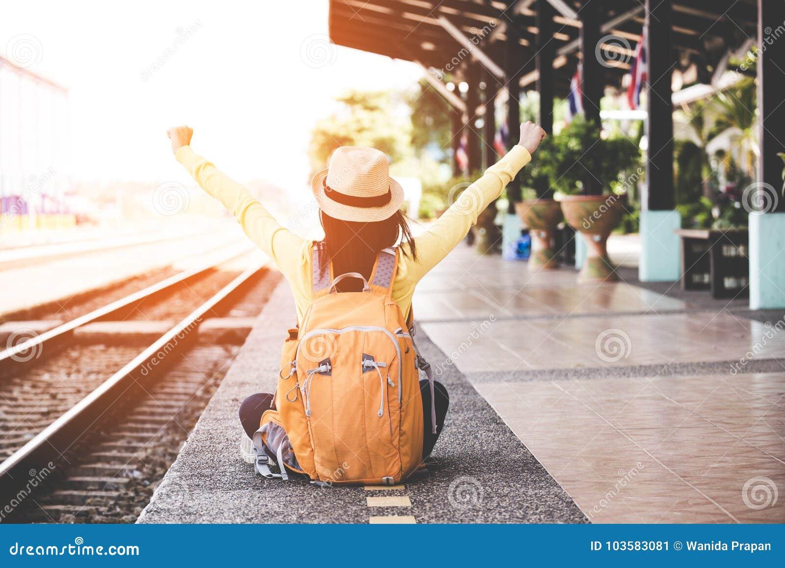 佩带背包的旅游亚裔生活方式妇女举行地图,旅客选址等待的火车,很愉快和放松