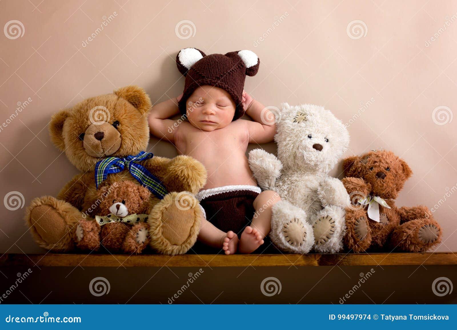 佩带褐色的新出生的男婴编织了熊帽子和裤子, sle