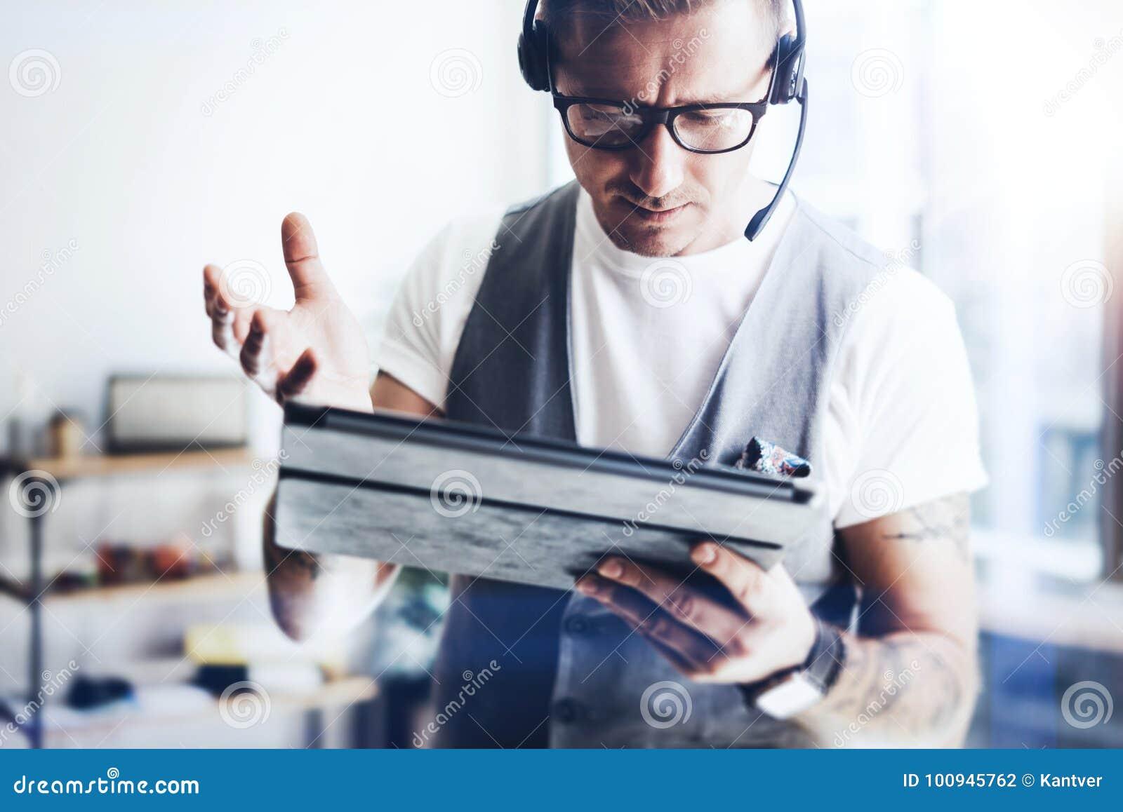 佩带音频耳机和做录影交谈的商人通过数字式片剂 工作在他的典雅的人数字式