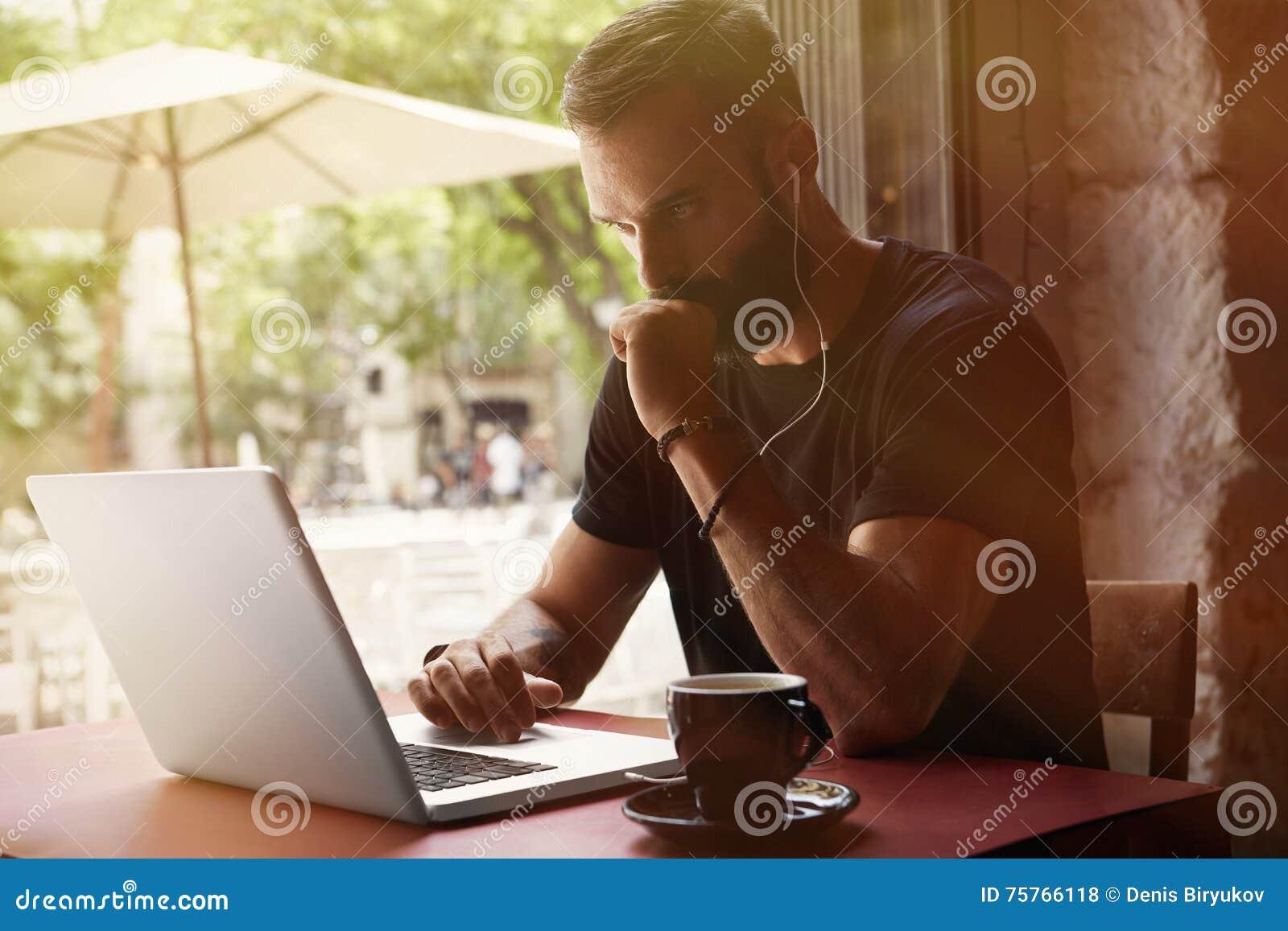 佩带黑T恤杉运作的膝上型计算机都市咖啡馆的被集中的年轻有胡子的商人 人坐的表杯咖啡