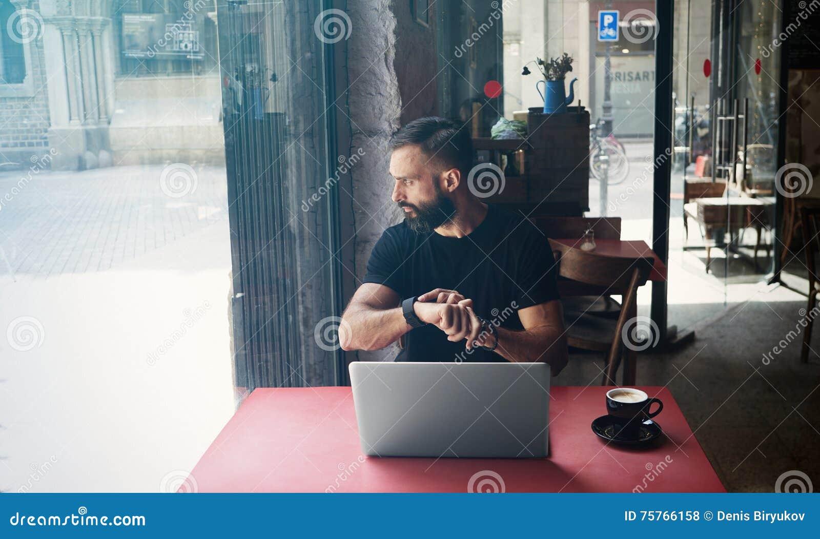 佩带黑T恤杉运作的膝上型计算机都市咖啡馆的年轻有胡子的商人 人坐的木表杯咖啡看