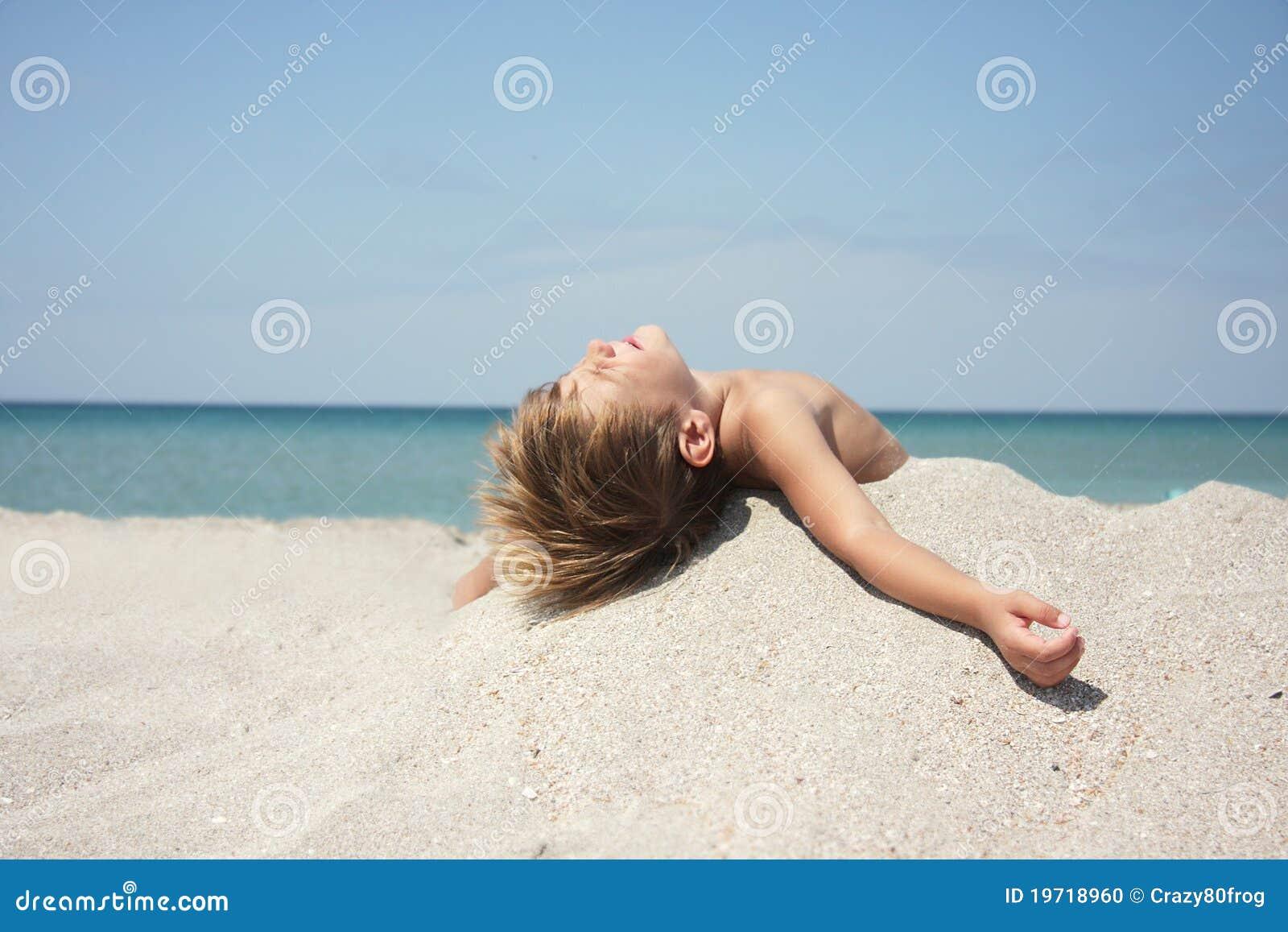 使晴朗男孩日热休息的沙子靠岸