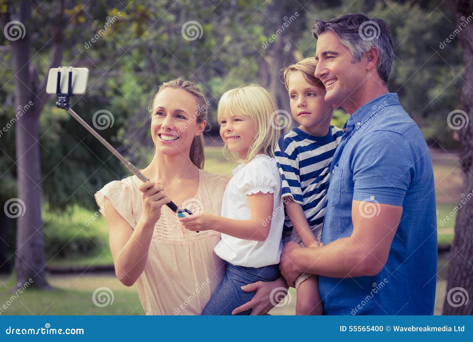 使用一根selfie棍子的愉快的家庭在公园
