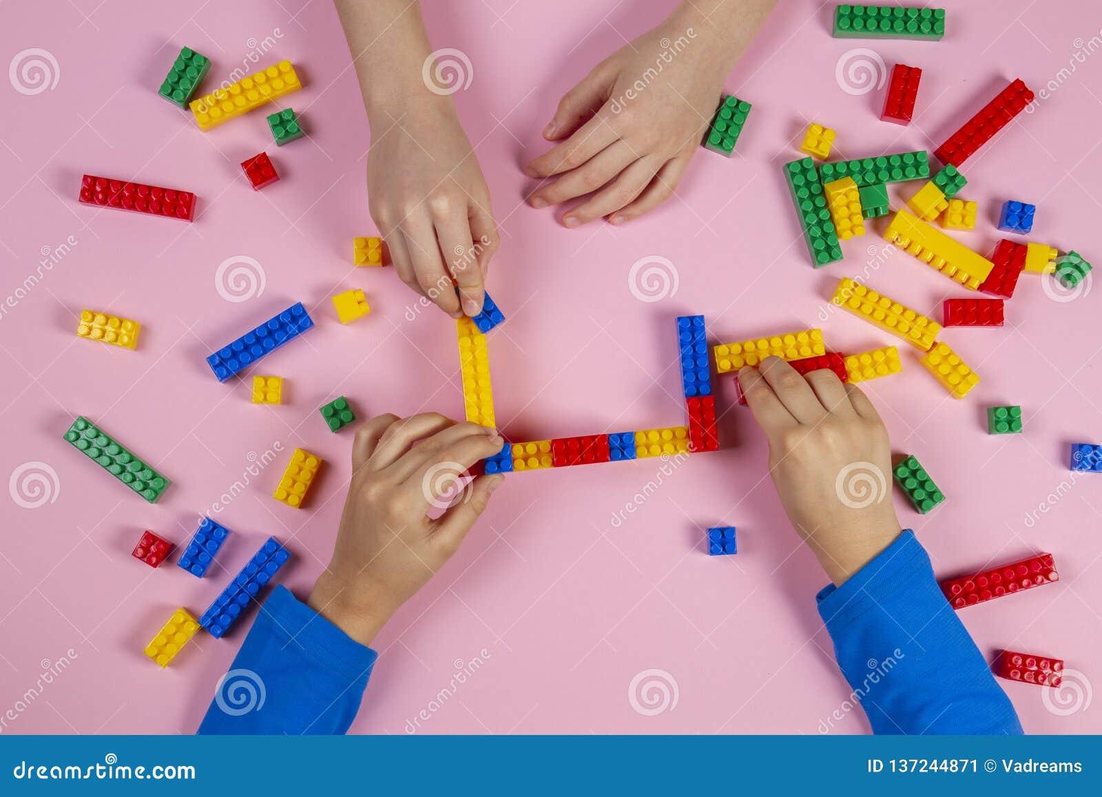 使用与五颜六色的在桃红色背景的大厦塑料砖的孩子 教育开发的玩具背景