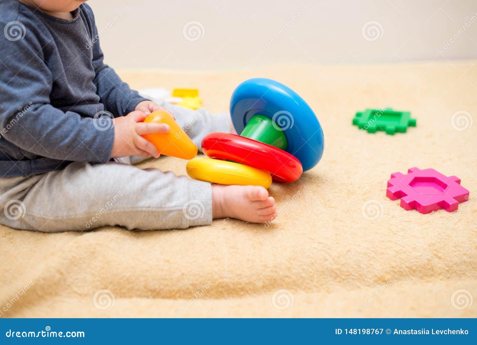 使用与五颜六色的玩具金字塔的可爱宝贝在轻的卧室 小孩的玩具 有教育玩具的孩子 o