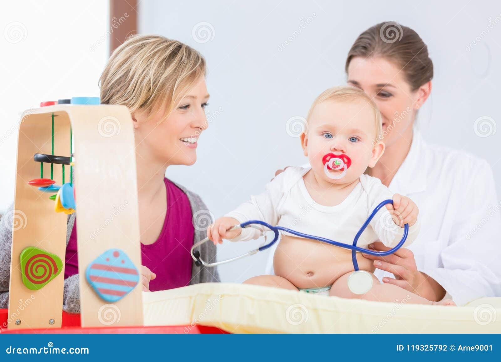 使用与听诊器的逗人喜爱和健康女婴在考试期间