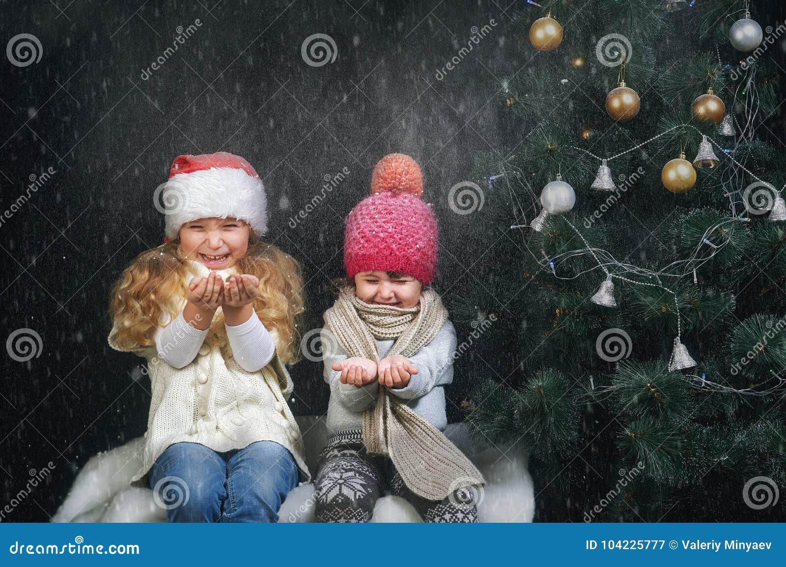使用与在黑暗的背景的雪花的孩子在圣诞树附近