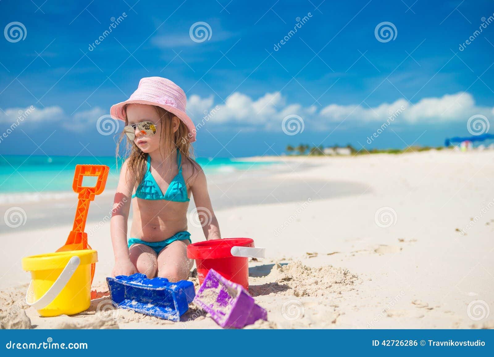 使用与在a的沙子的可爱的小女孩
