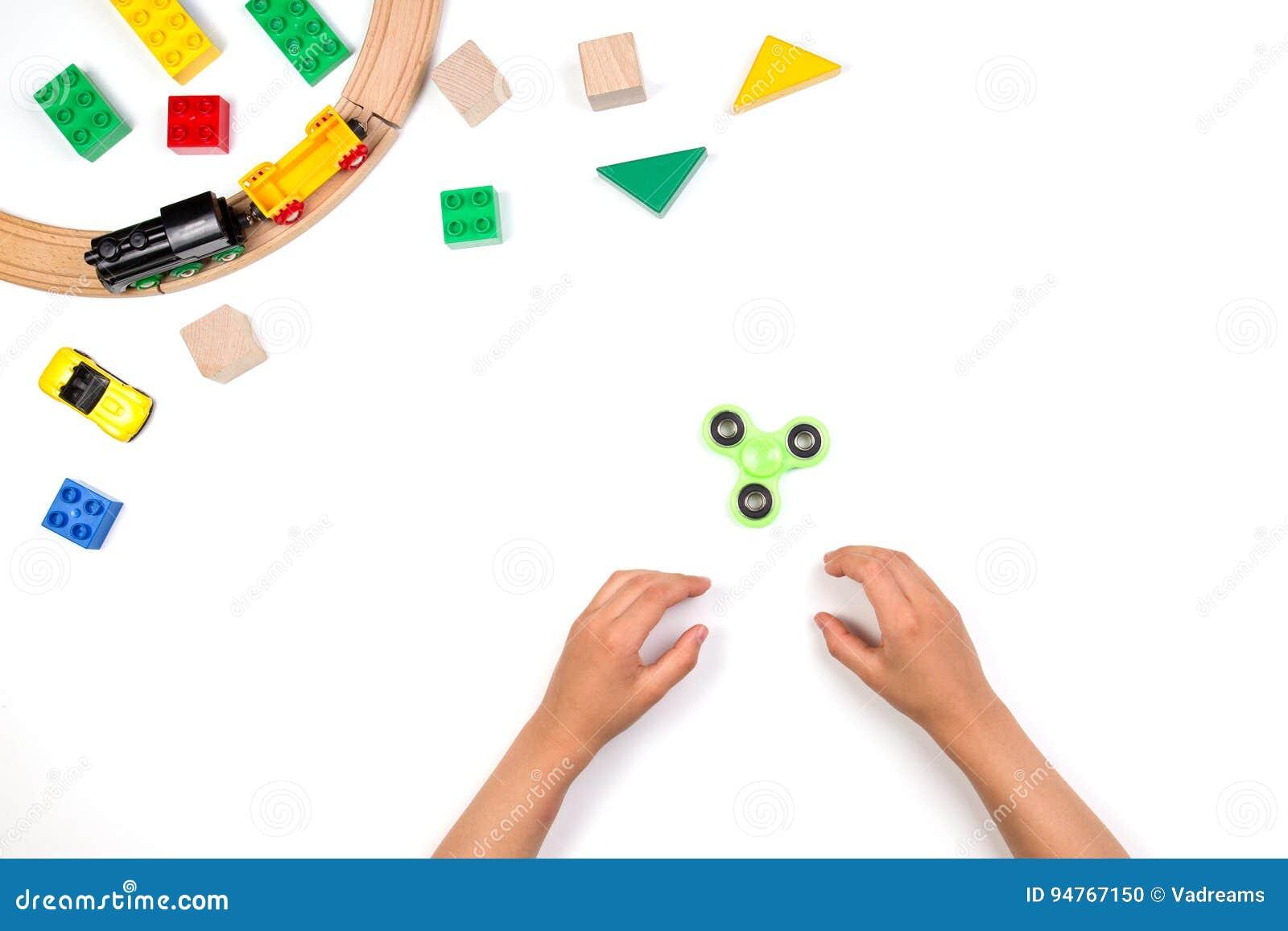 使用与坐立不安锭床工人玩具的孩子手 在白色背景的许多五颜六色的玩具