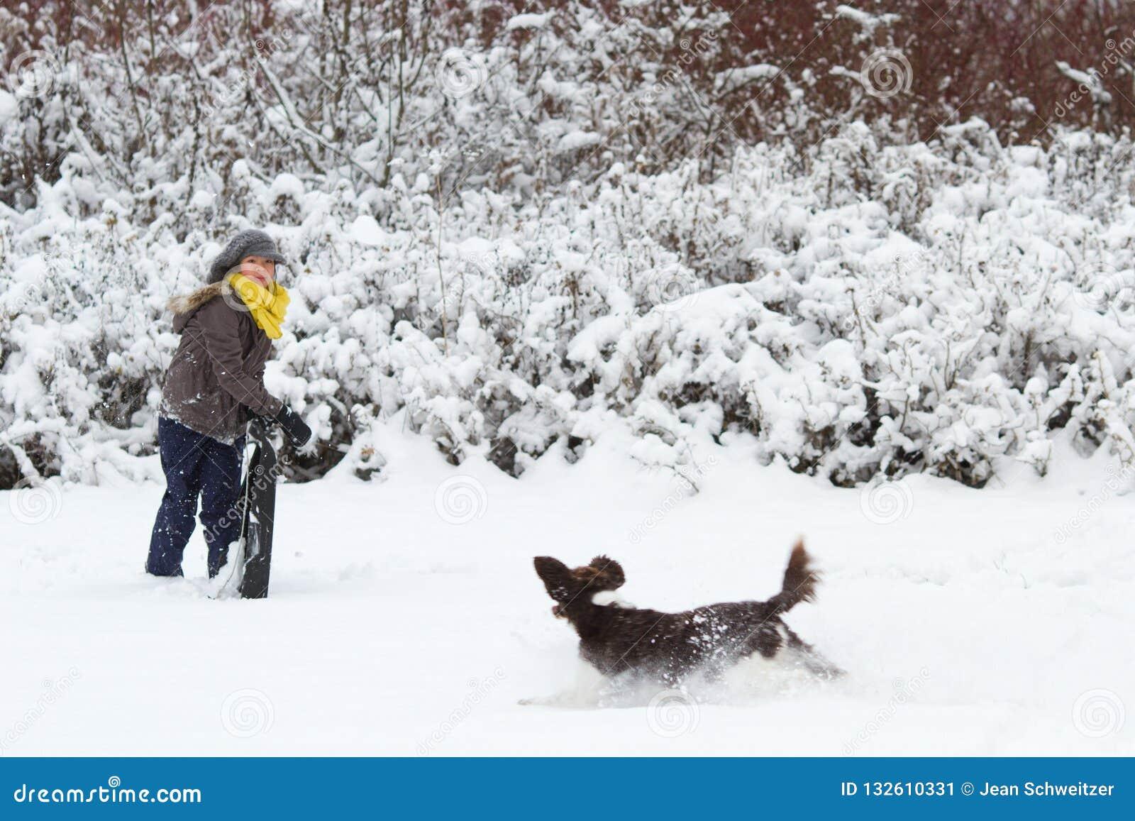 使用与她的在雪的狗的女孩