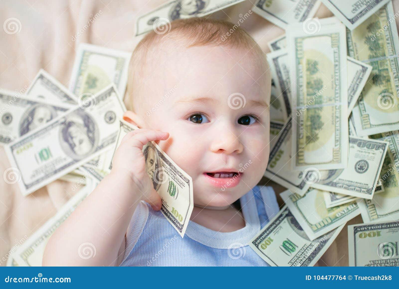 使用与很多金钱的逗人喜爱的男婴喜欢谈在电话,美国人一百美元现金