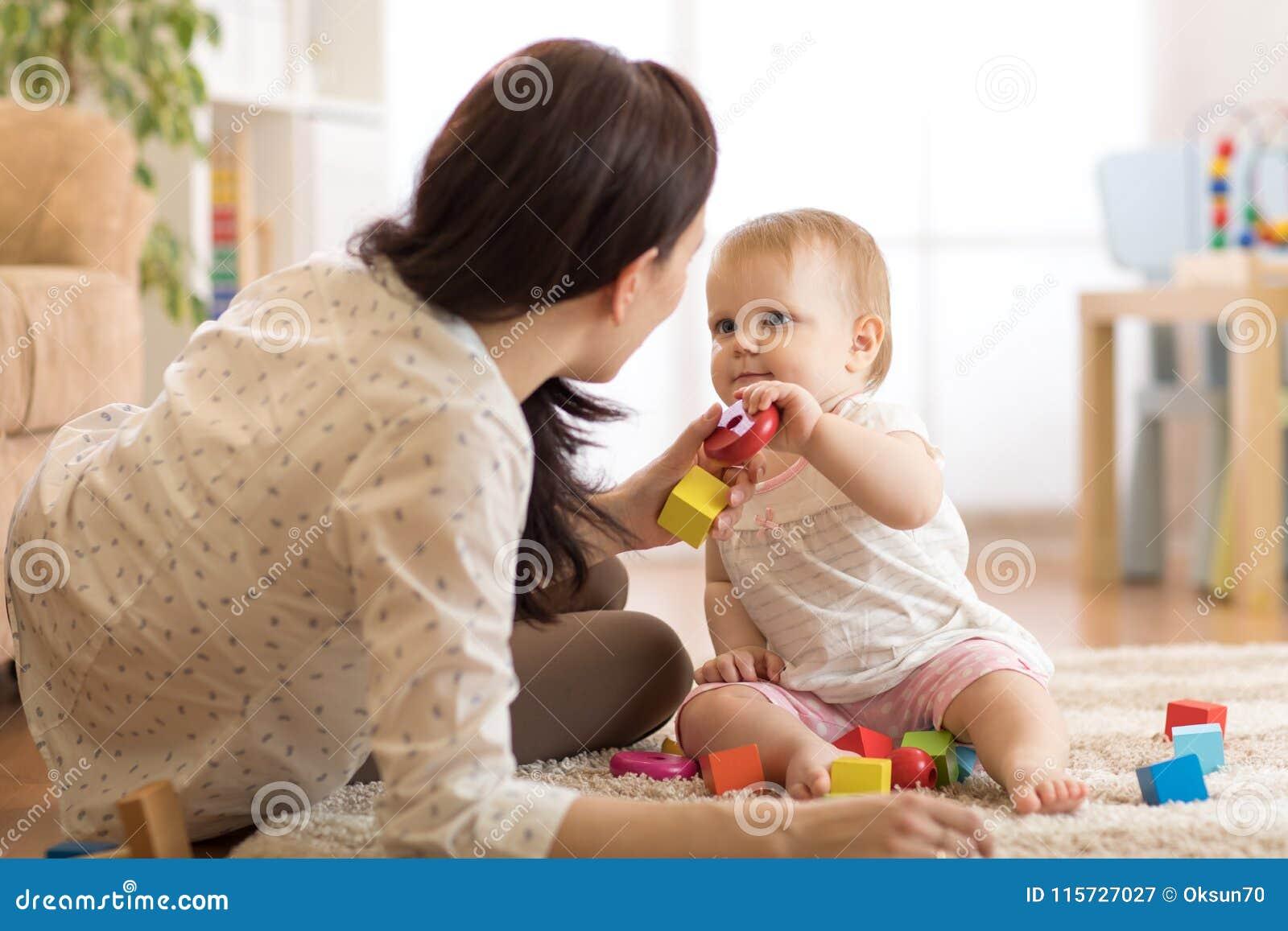 使用与教育玩具的可爱的女婴在托儿所 获得的孩子与五颜六色的不同的玩具的乐趣在家