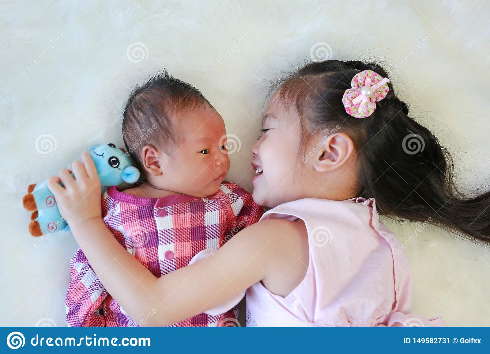 使用与新生儿的亚裔姐妹说谎在白色毛皮背景