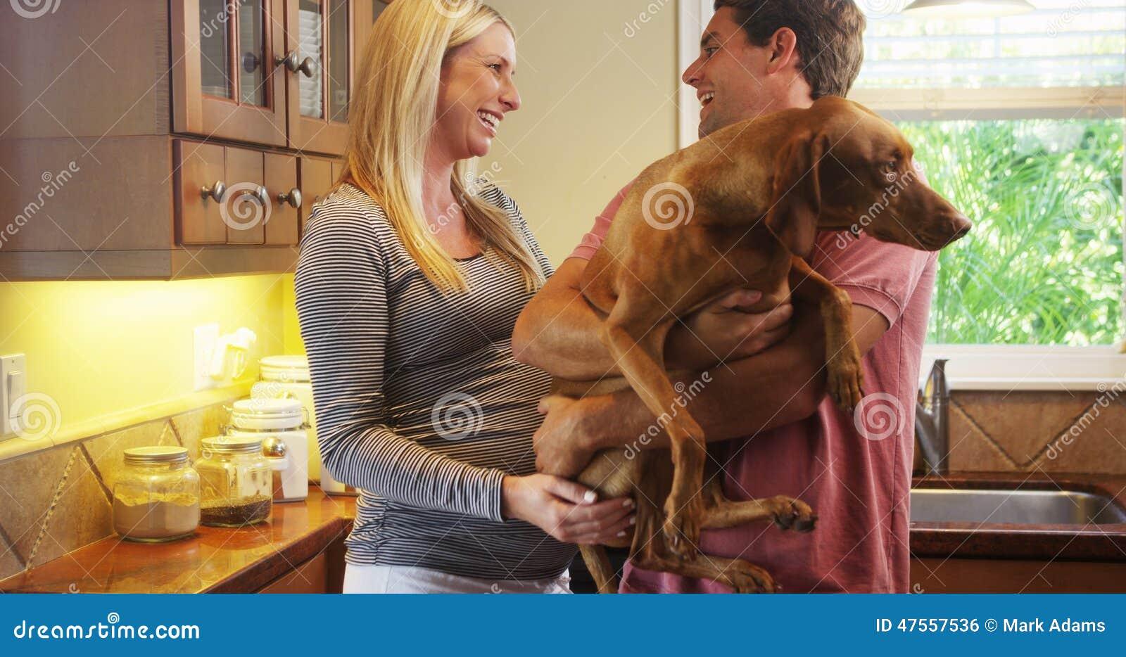 孕和狗干电影_在家使用与狗的美好的怀孕的夫妇在厨房里.