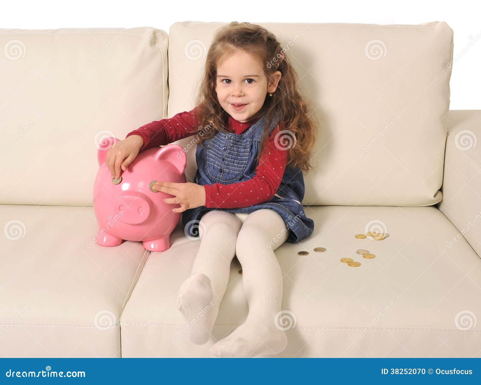 使用与硬币和巨大的存钱罐的逗人喜爱的小女孩沙发的