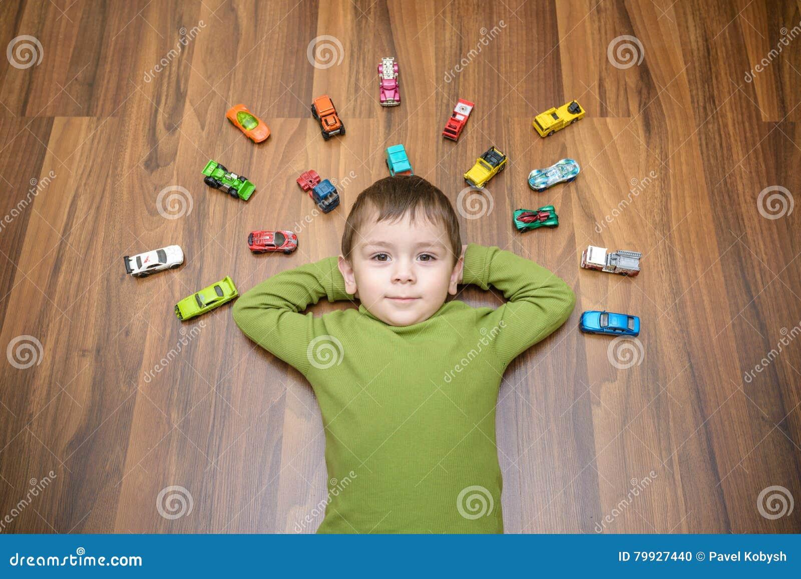 使用与许多的小白种人孩子室内玩具汽车 穿绿色衬衣的孩子男孩 愉快学龄前有乐趣在家或nu