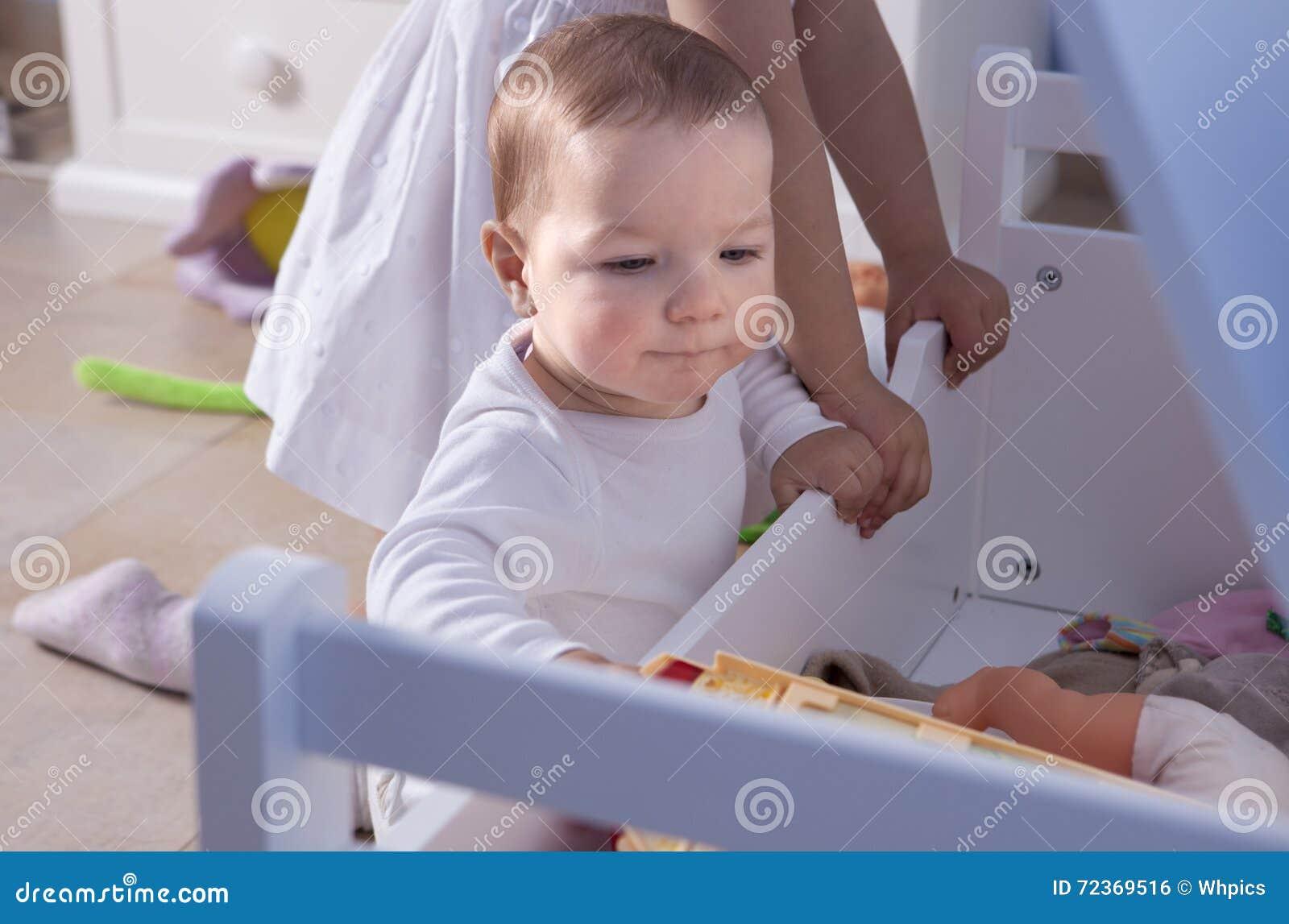 使用与他的姐妹的男婴在玩具室