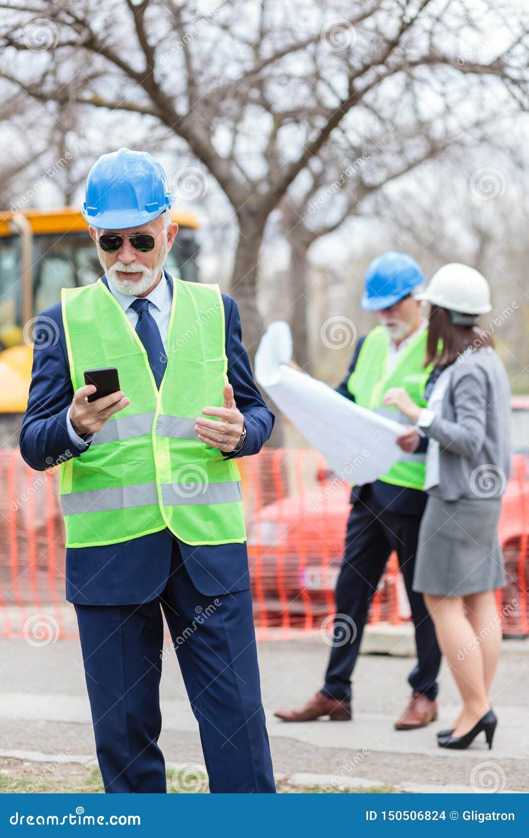 使用他的智能手机的严肃的高级工程师或商人,当检查工地工作时 看的两人