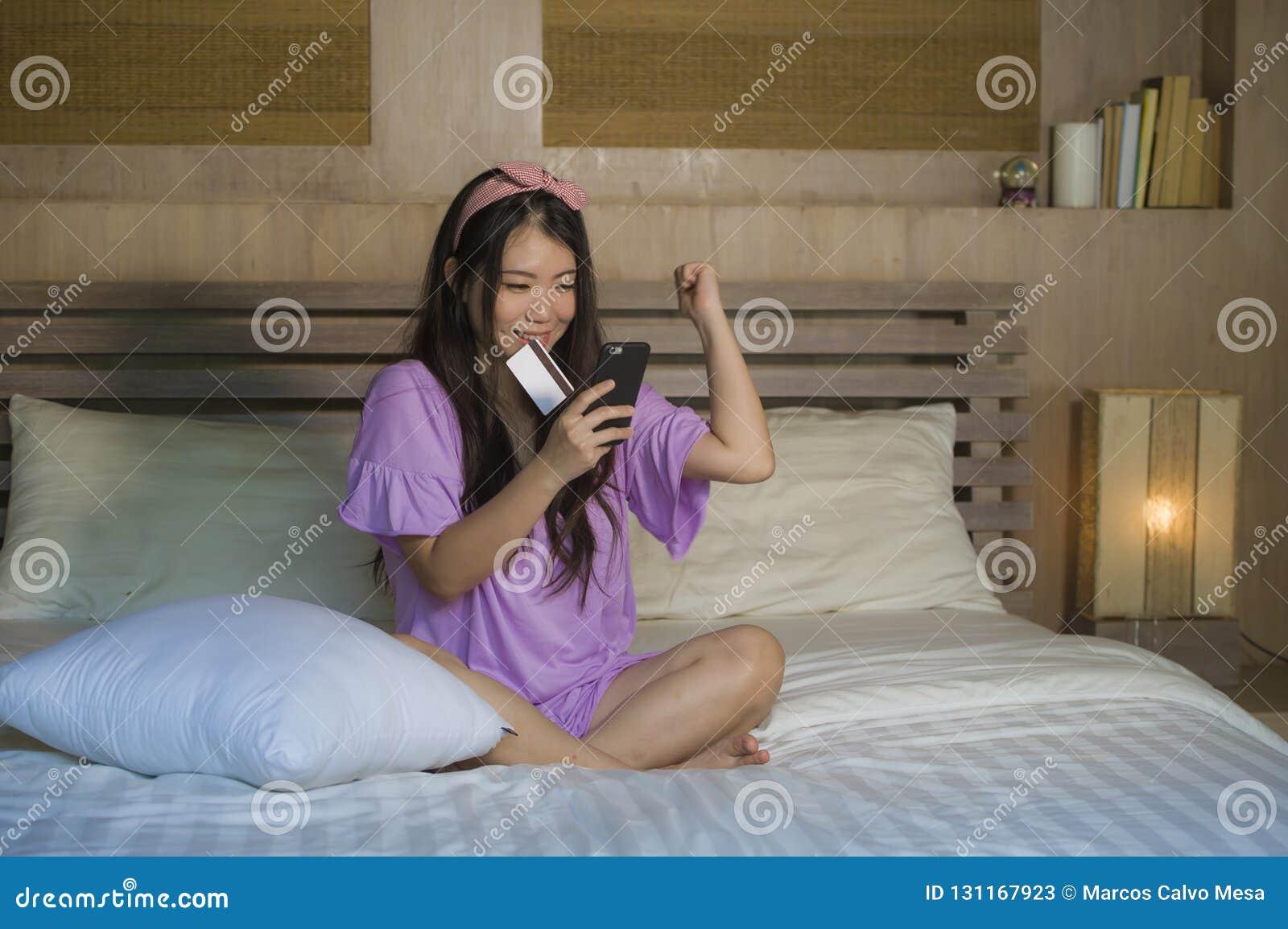 使用信用卡网上银行的年轻美丽和愉快的亚洲韩国女人在家卧室与手机在床微笑的o上