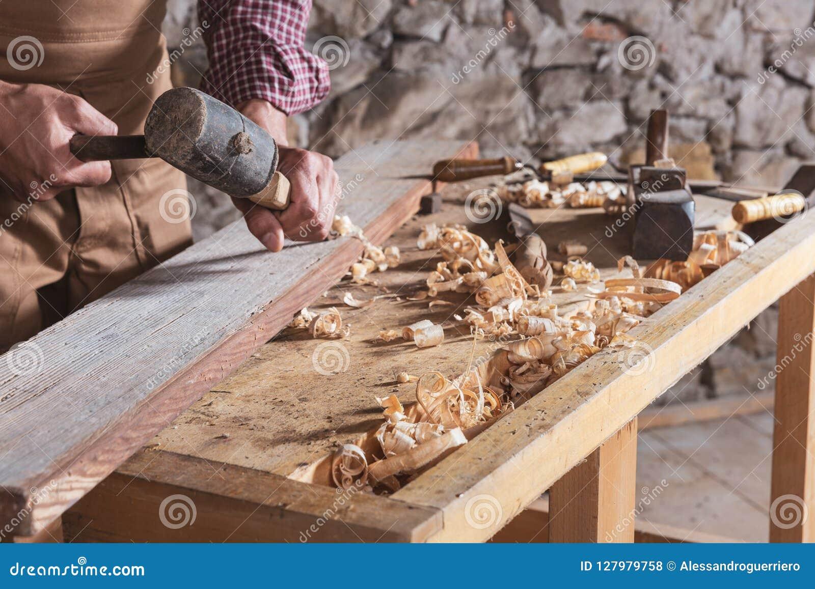 使用凿子的木工使光滑在木头下