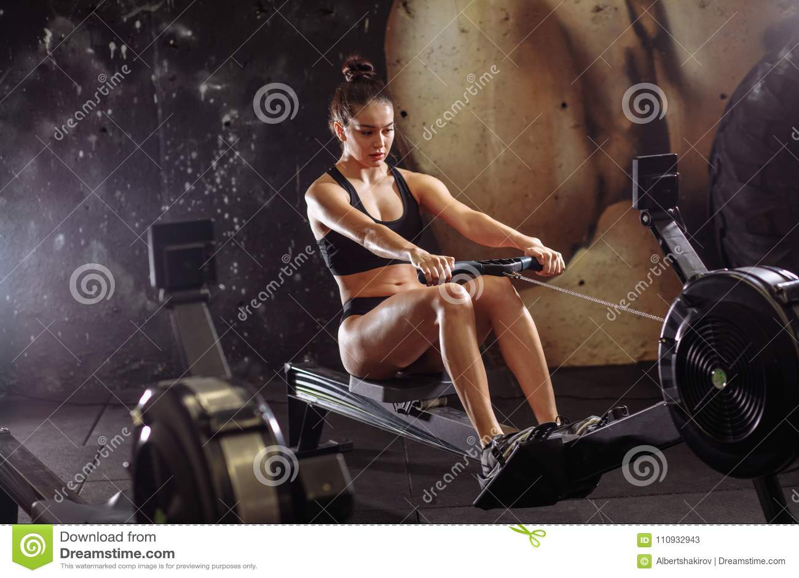 使用划船器的女性在健身房 做在健身俱乐部的妇女心脏锻炼
