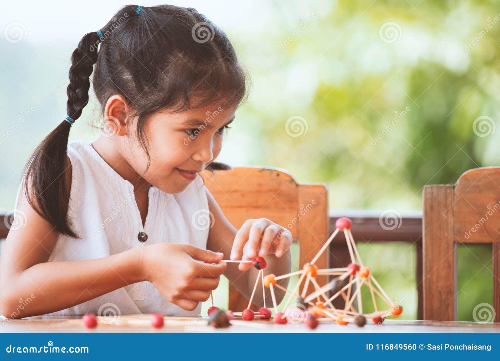 使用和创造用戏剧面团的逗人喜爱的亚裔儿童女孩