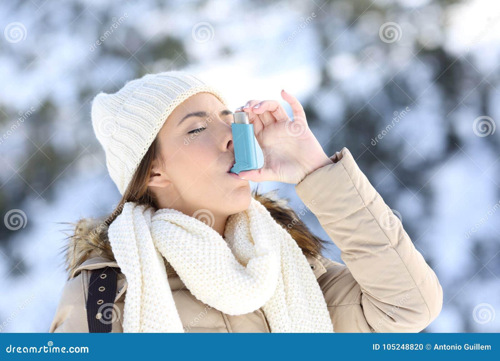 使用哮喘吸入器的妇女在一个冷的冬天