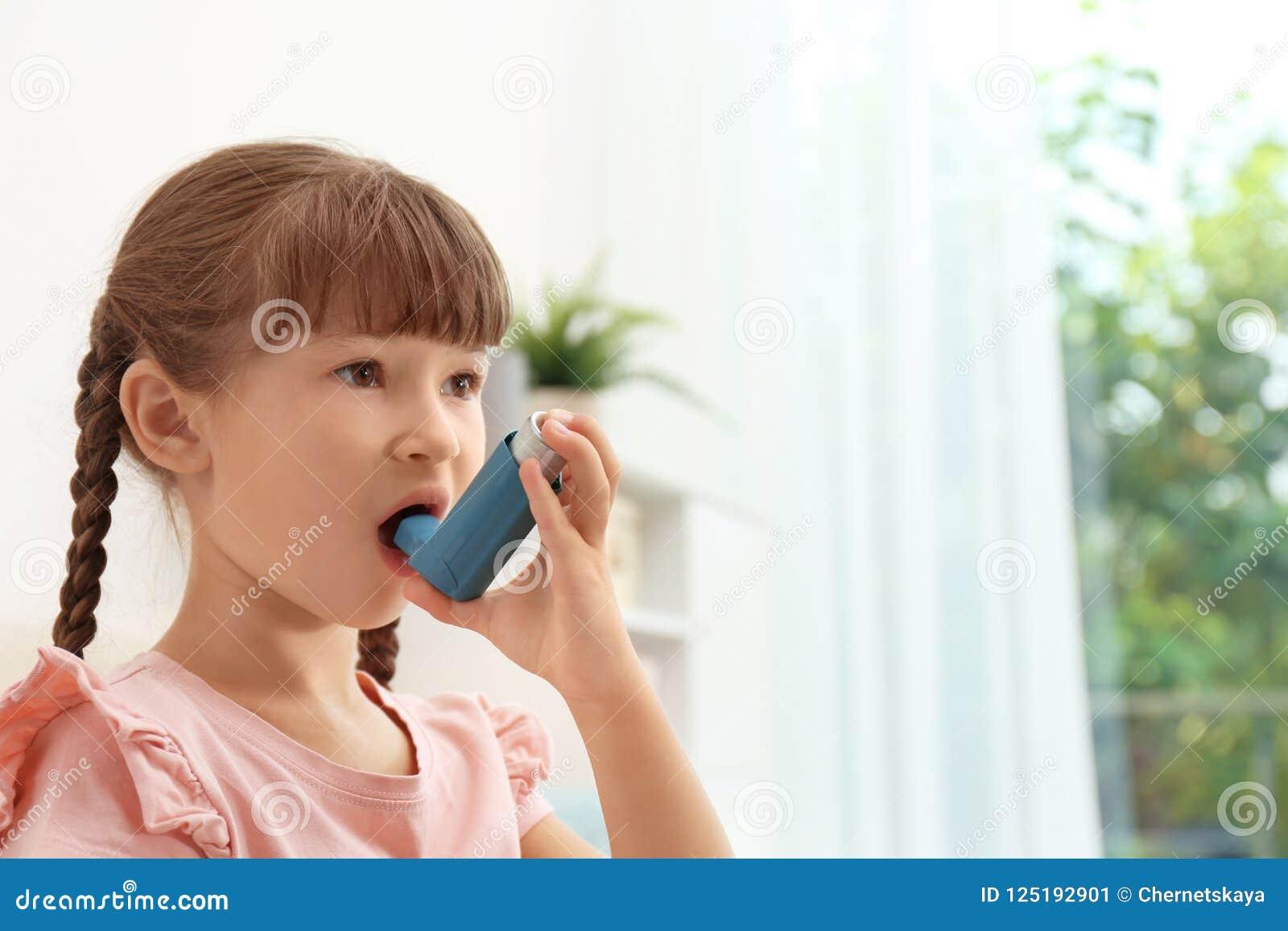 使用哮喘吸入器的小女孩