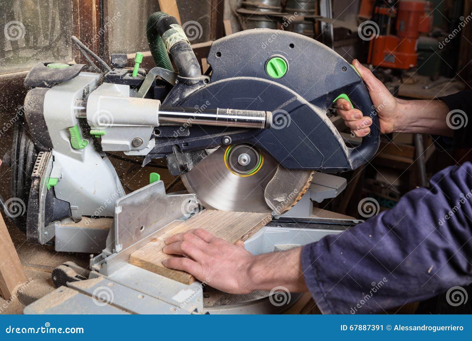 使用圆锯的木匠的手