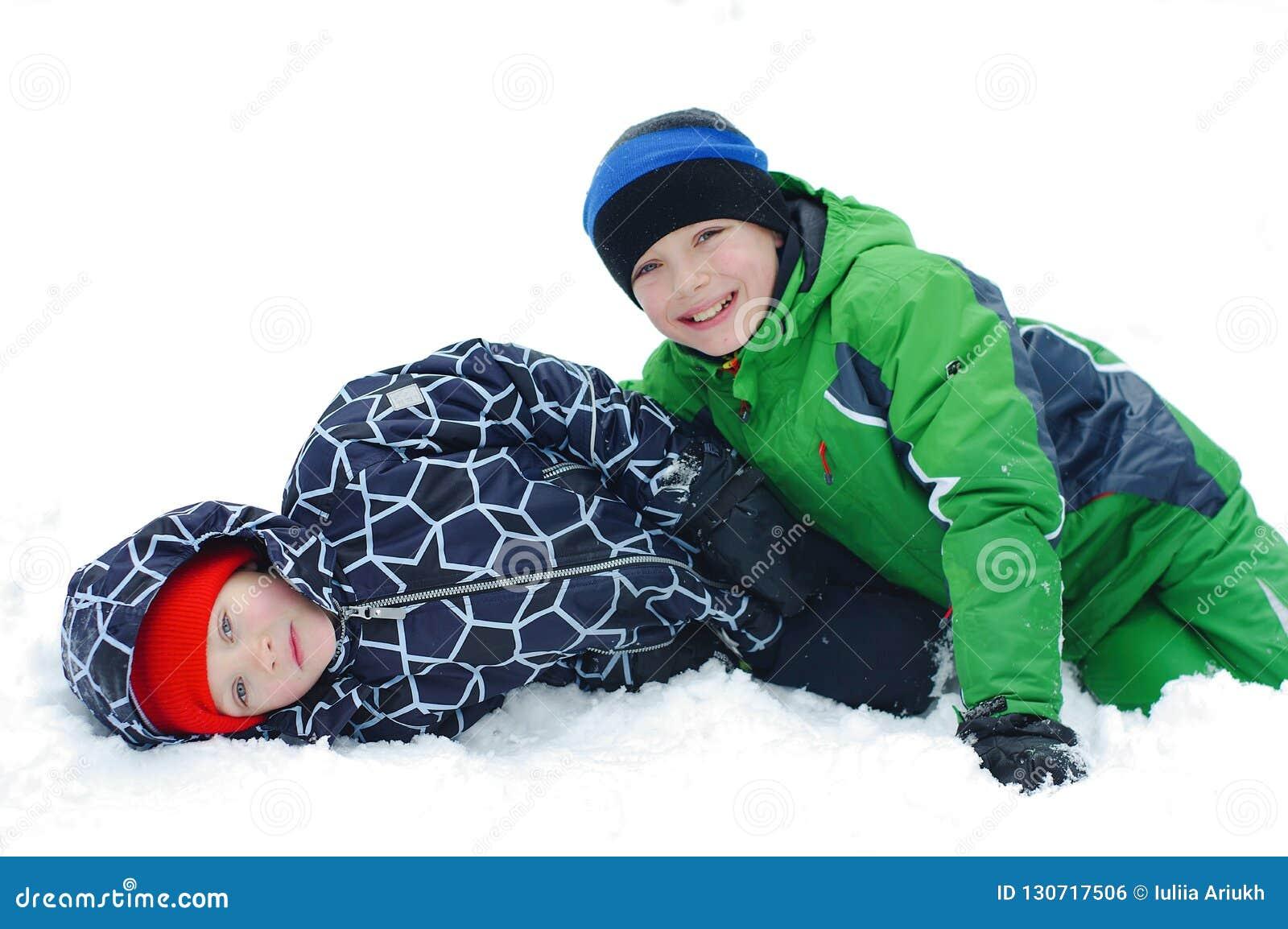 使用在冬天步行的愉快的男孩本质上 孩子跳和获得乐趣在冬天公园