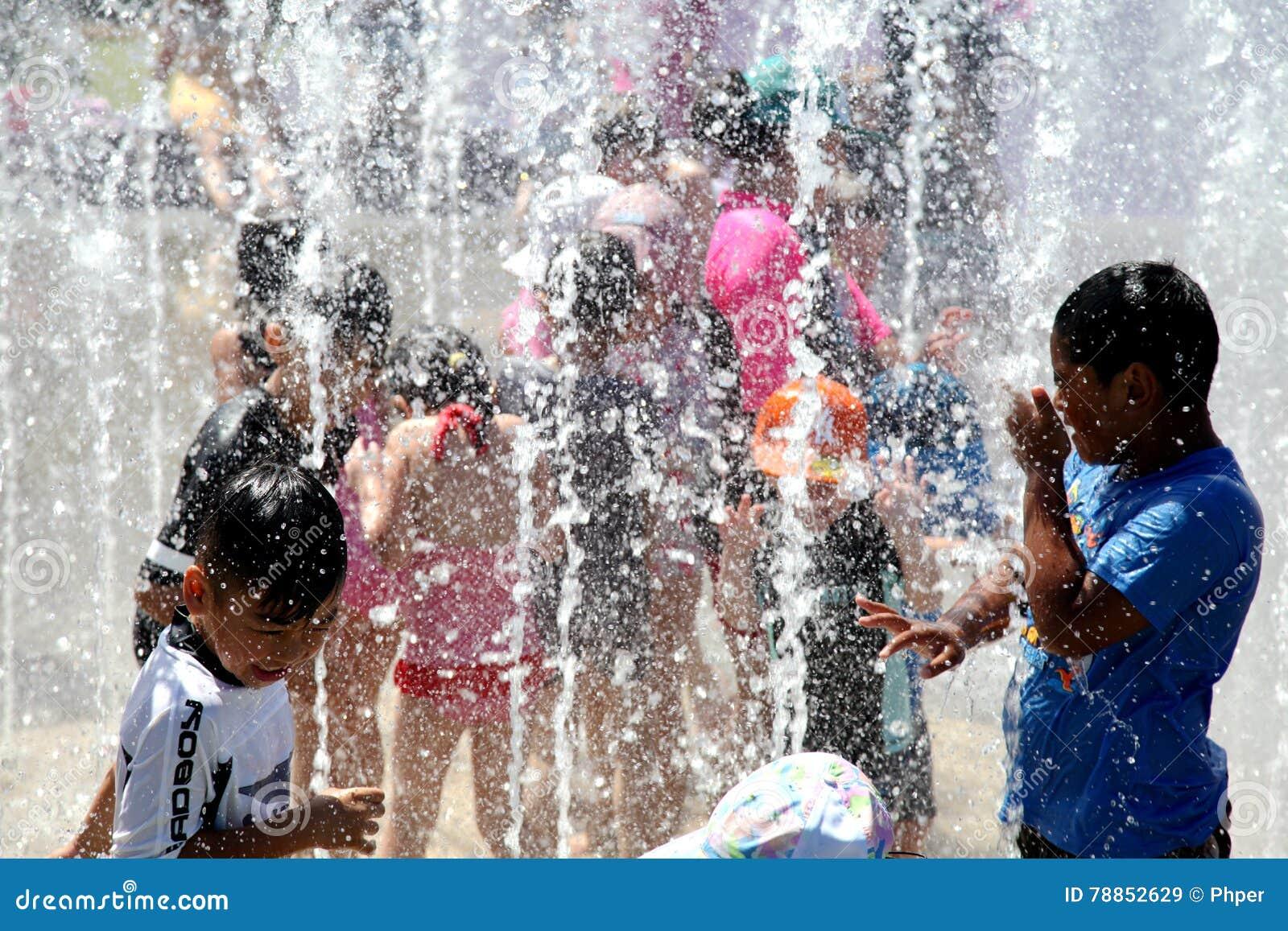 使用在喷泉的孩子在一热的天