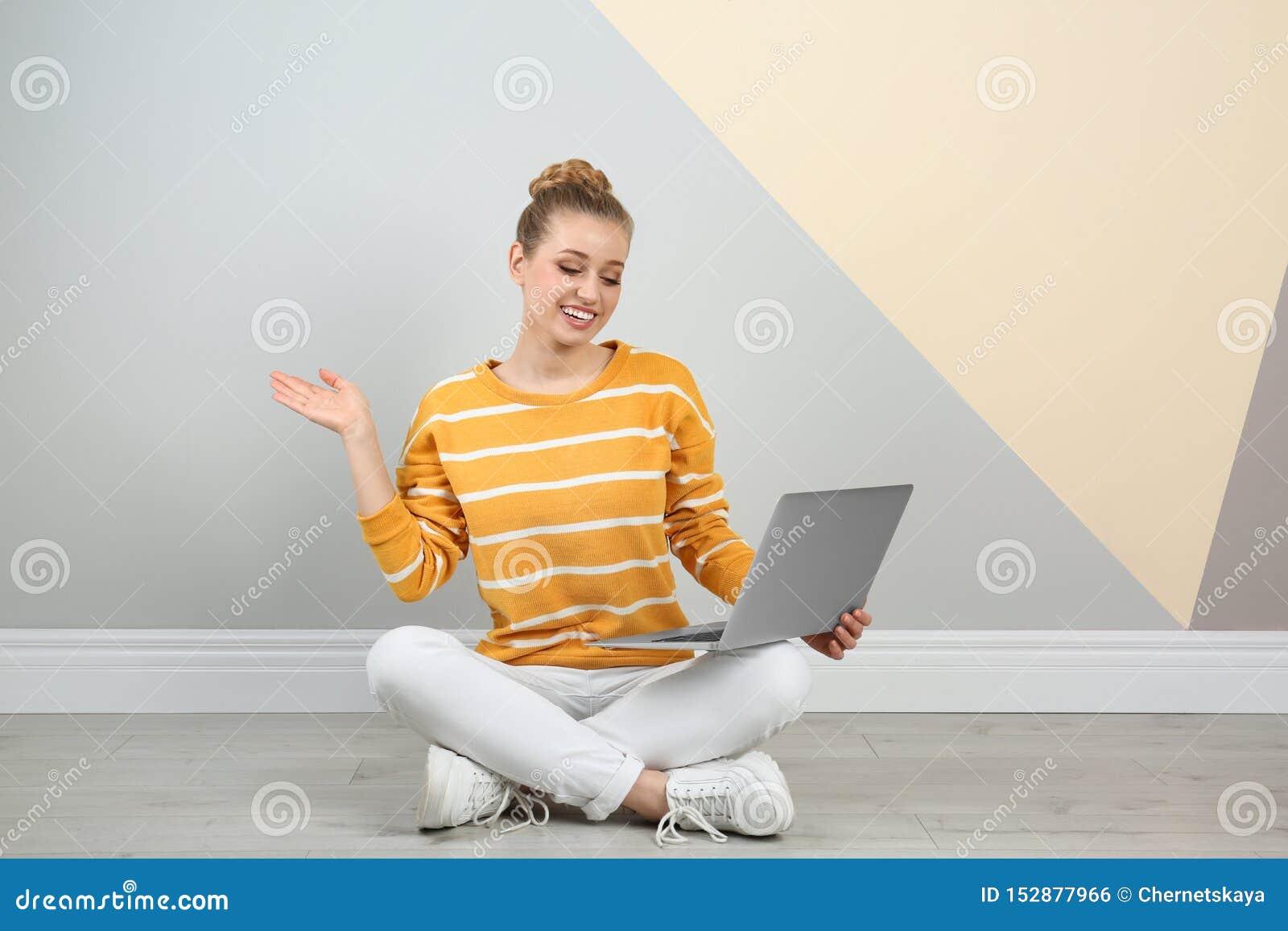 使用在地板上的年轻女人膝上型计算机