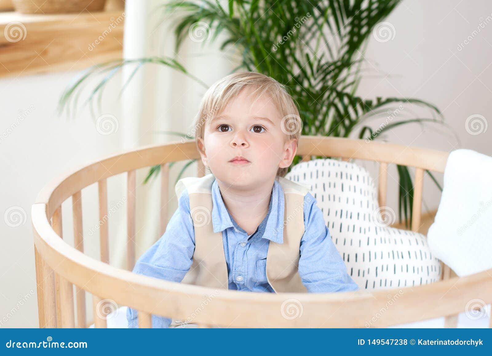 使用在婴儿床的一个愉快的男孩的画象 男孩在一个小儿床单独坐在托儿所 孤独的孩子在小儿床停留 Lo