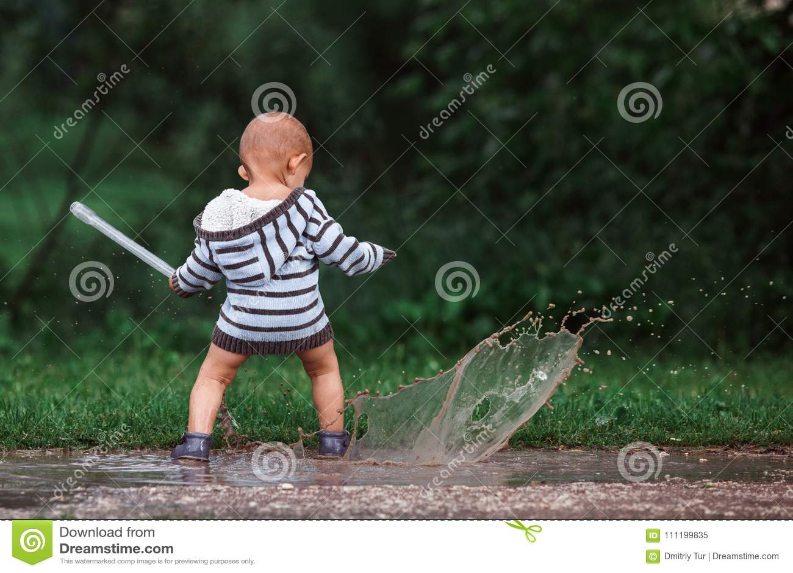 使用在水坑的小男孩在夏天节日,波多利斯克7月2017年,俄罗斯音乐的春天森林里