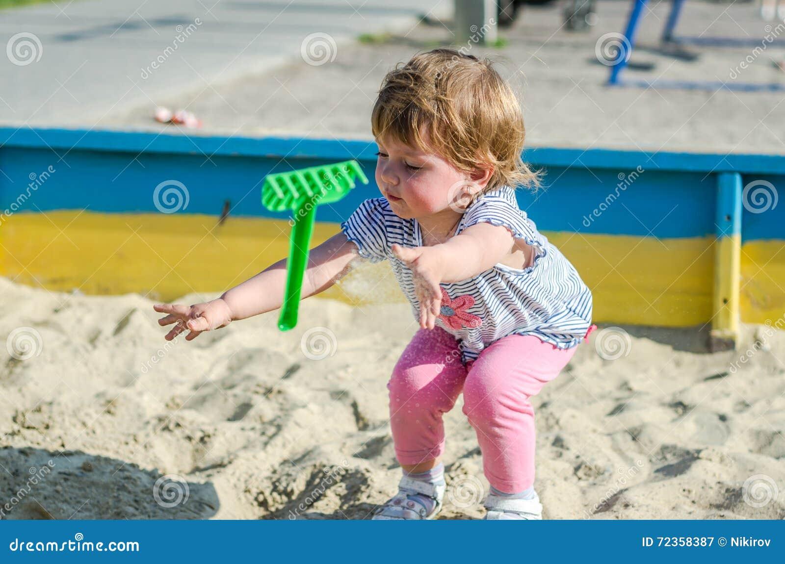 使用在沙盒沙子土墩的操场的小迷人的女孩婴孩在有铁锹和犁耙的桶