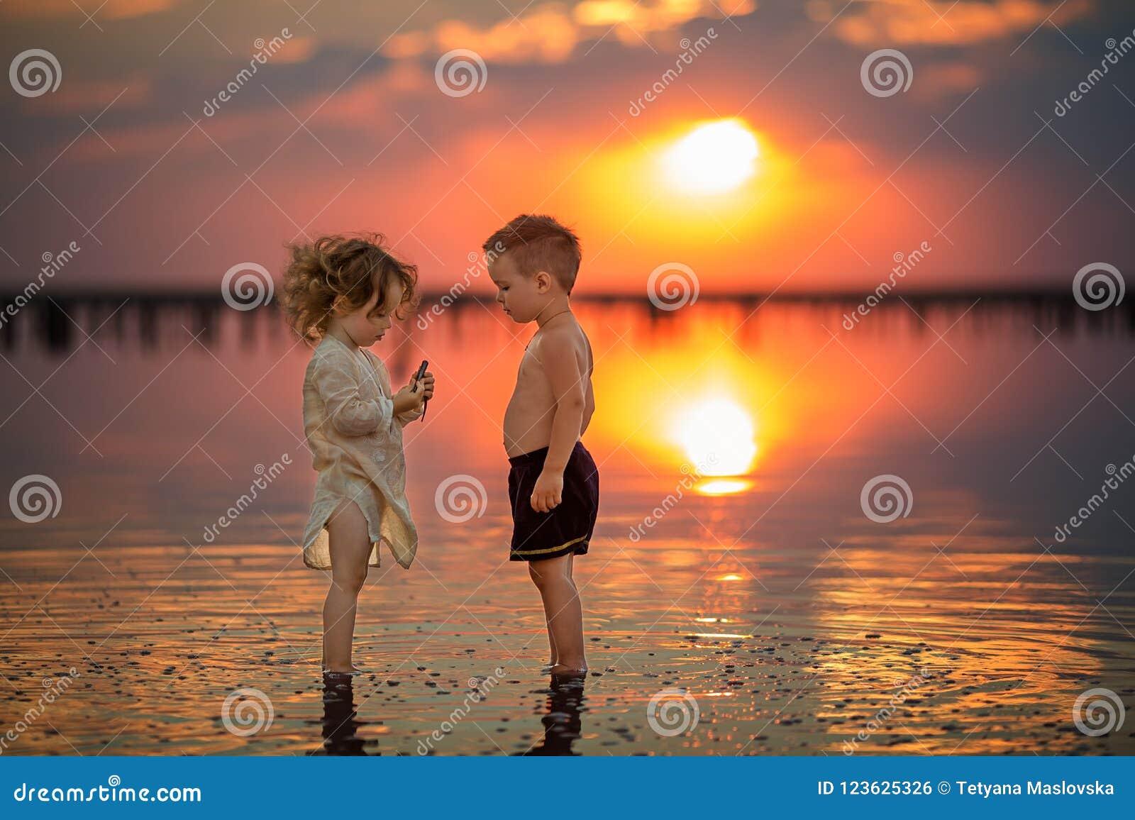 使用在海滩的两个小孩在日落期间 反映在水中