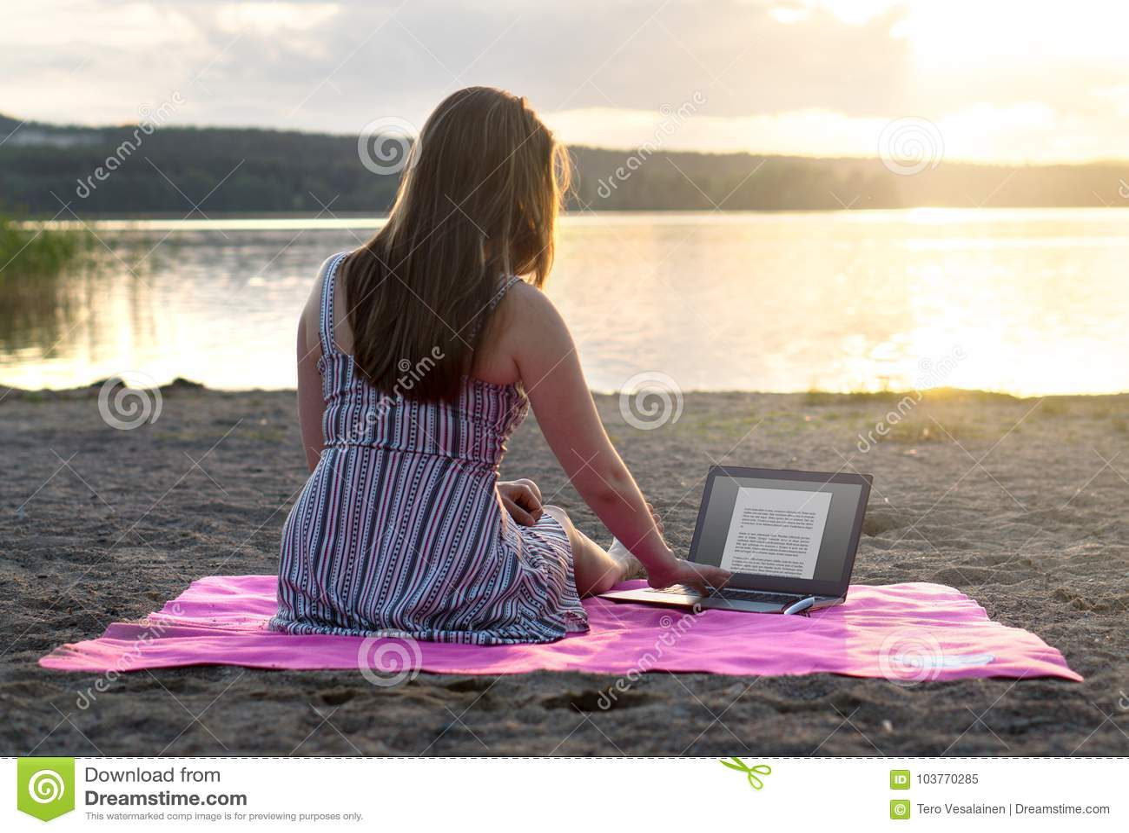 使用在海滩的年轻可爱的妇女膝上型计算机在日落