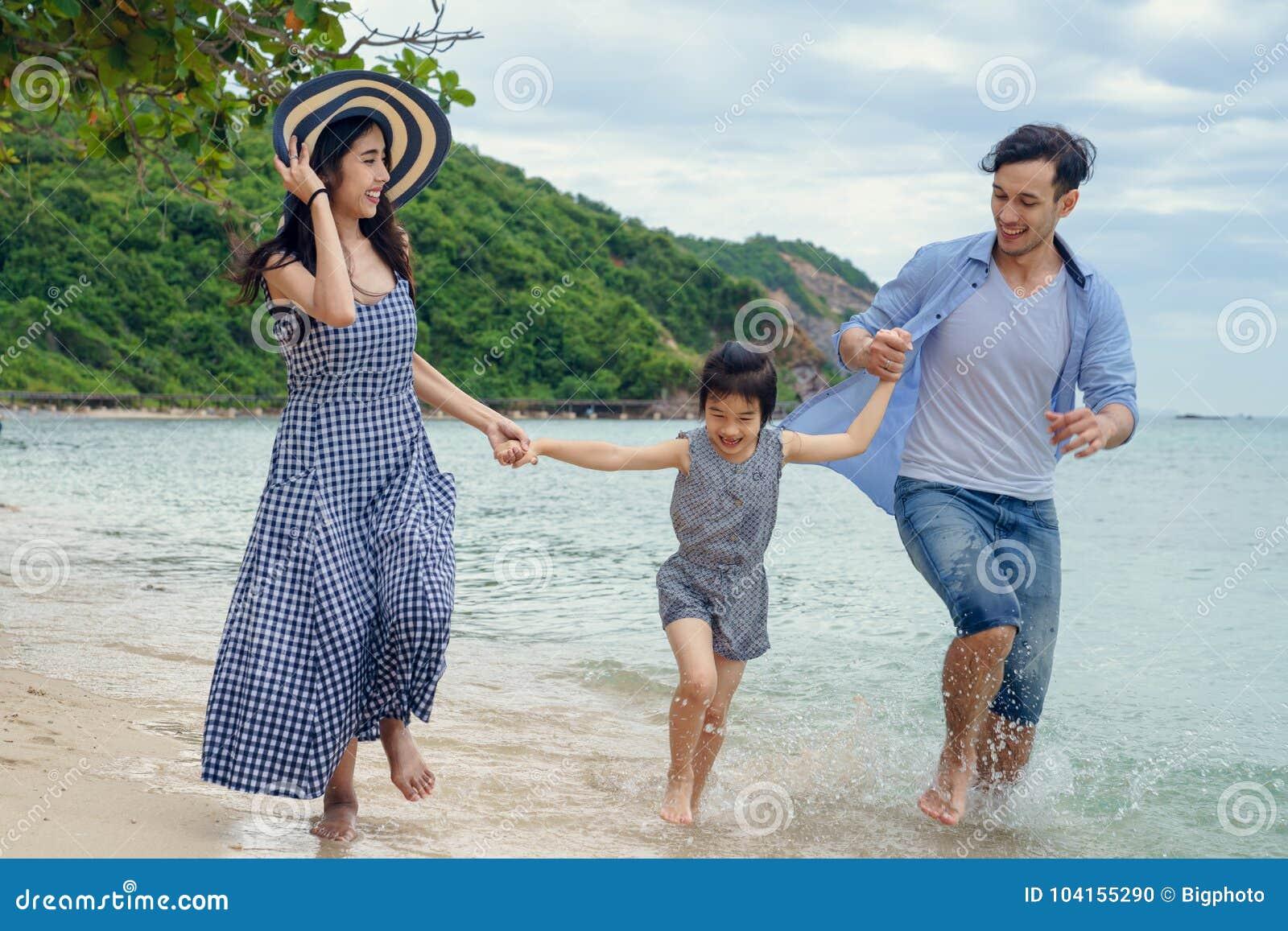 使用在海滩的愉快的家庭在天时间