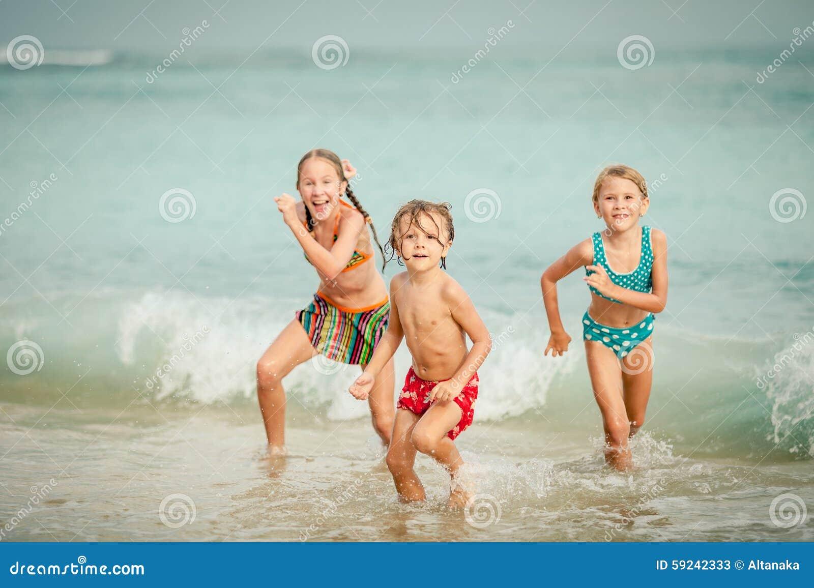 使用在海滩的三个愉快的孩子
