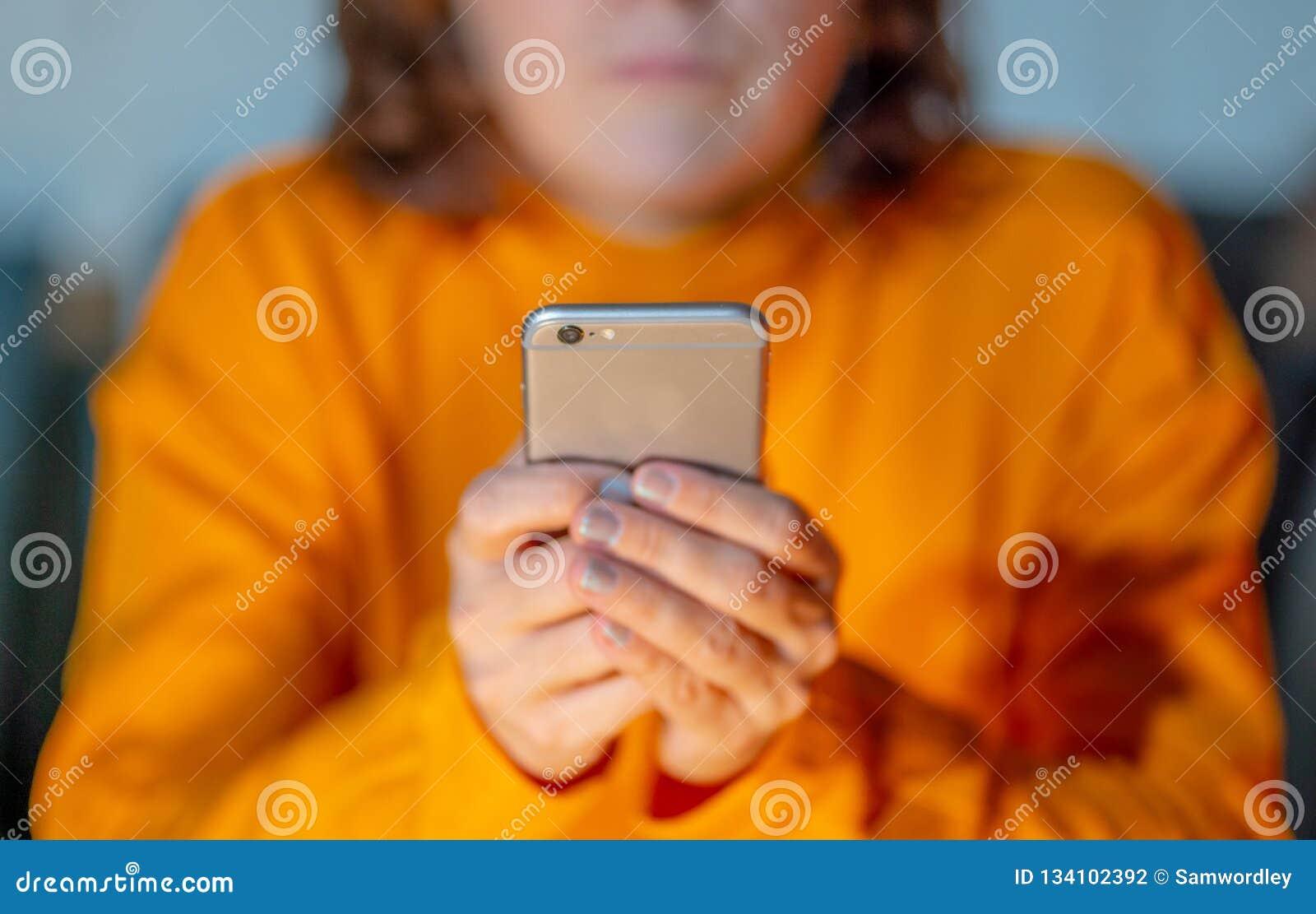 使用在电话瘾和流动赌博概念的智能手机关闭年轻女人手