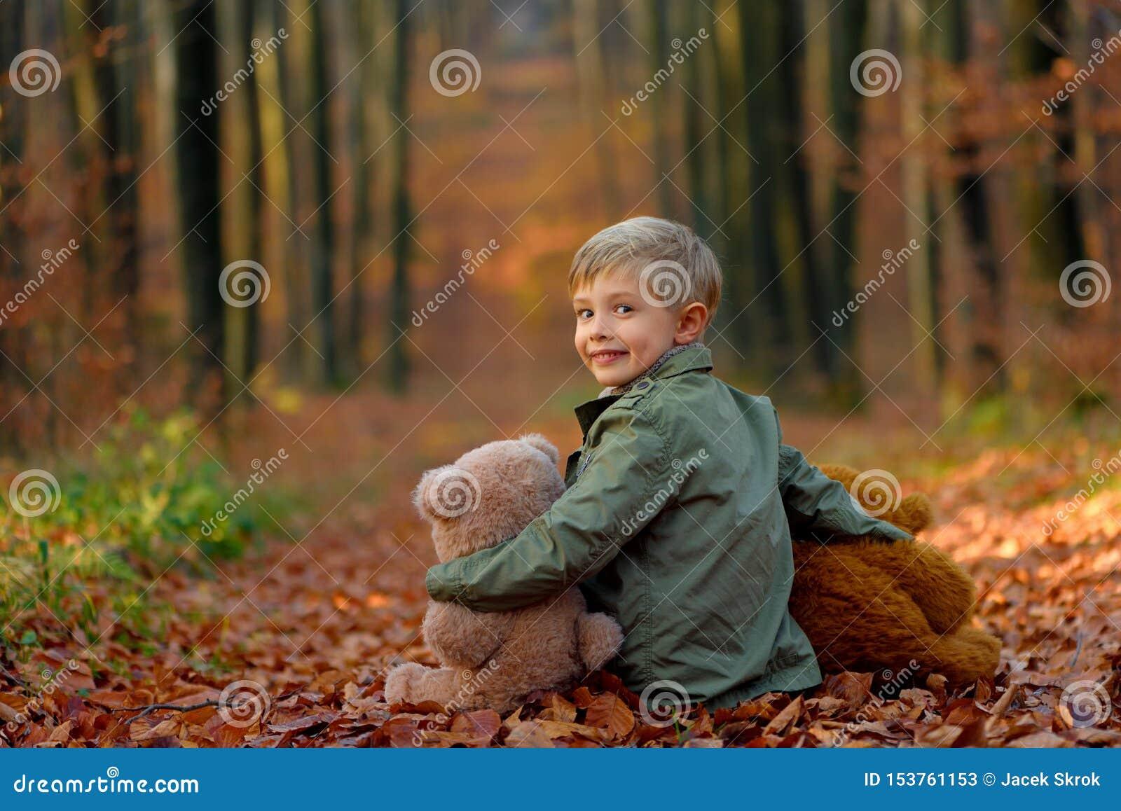 使用在秋天公园的一个小男孩