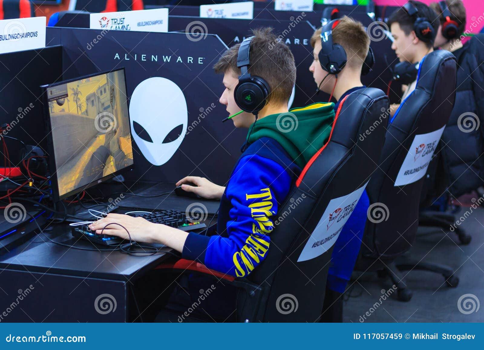 使用在计算机的耳机的年轻游戏玩家