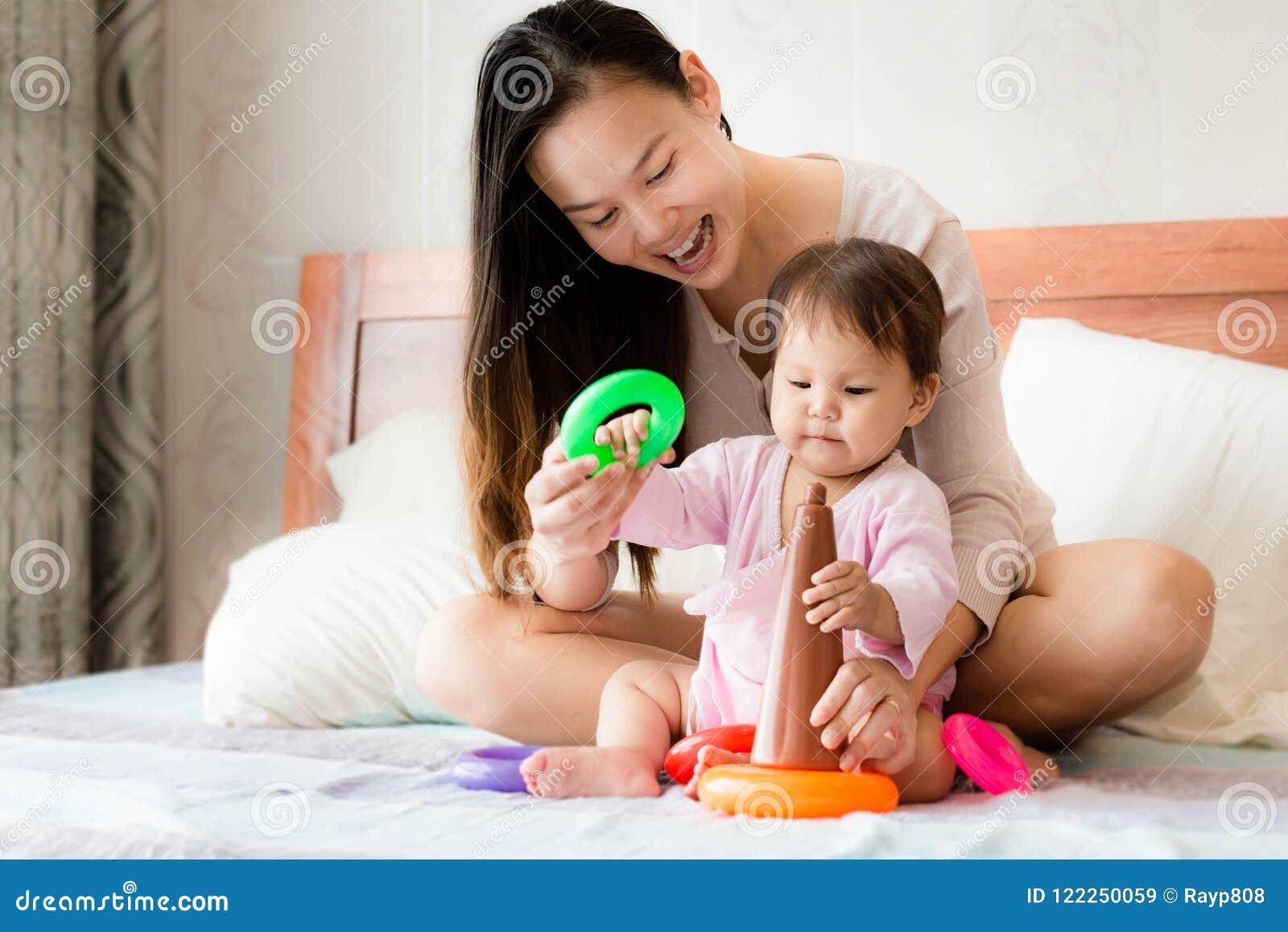 使用塑料箍玩具,愉快的母亲教两岁的女儿协调技能