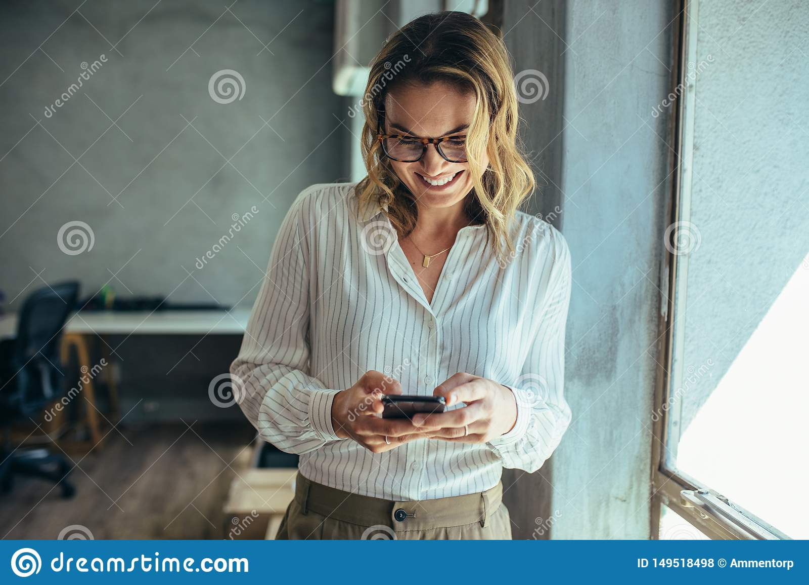 使用她的智能手机的女实业家在办公室